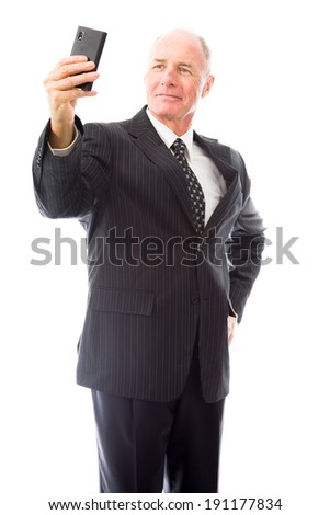 Businessman photographing self with a mobile phone