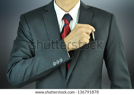 Businessman picking a pen from the pocket - stock photo