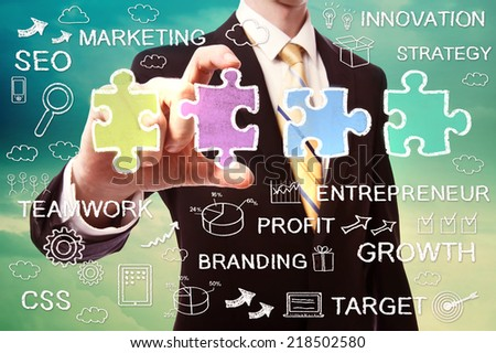 Businessman pinching a piece of the puzzle with business ideas - stock photo