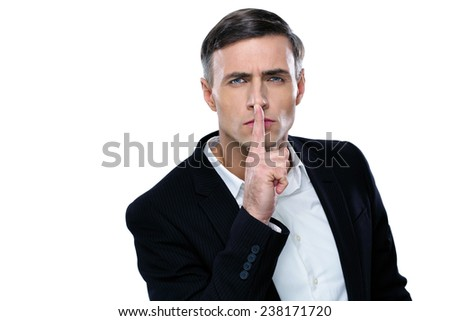 Businessman placing finger on lips saying shhh, be quiet! - stock photo