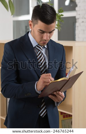Businessman planning and taking notes at his office - stock photo