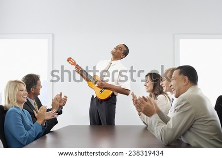Businessman Playing Guitar in a Business Meeting - stock photo
