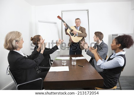 Businessman playing guitar in business meeting - stock photo