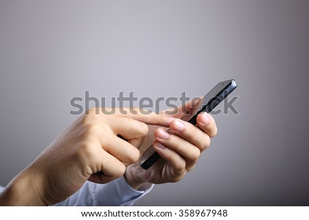 Businessman playing smart phone with gradually varied background. - stock photo