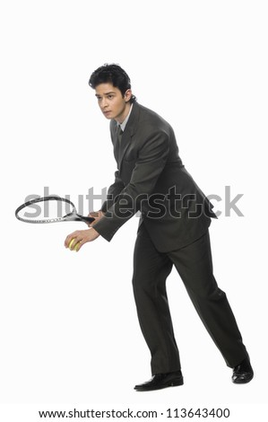 Businessman playing tennis - stock photo