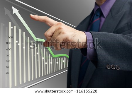 Businessman point at the top of the graph on screen