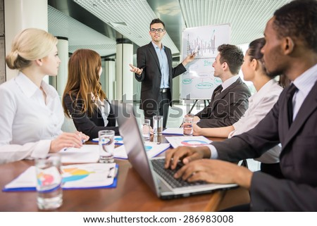 Businessman pointing at a growing chart during a meeting, - stock photo