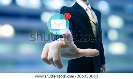 Businessman pointing at an email icon on blurred city background - stock photo