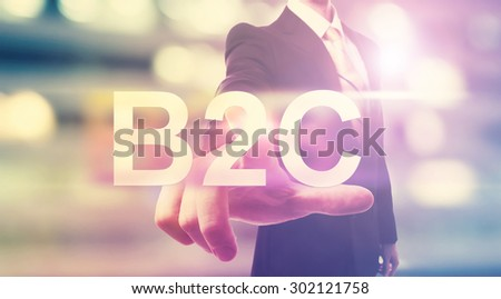 Businessman pointing at B2C (business to consumer) on blurred city background - stock photo