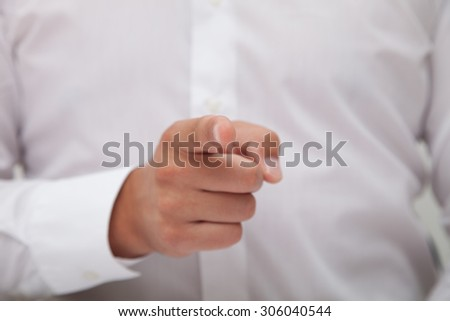 Businessman pointing at camera with his finger.