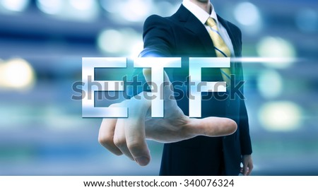 Businessman pointing at ETF (Exchange Traded Funds) on blurred city background - stock photo