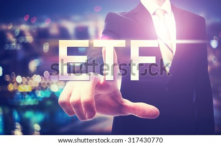 Businessman pointing at ETF on blurred city background - stock photo