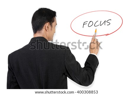 "Businessman pointing at ""Focus"" handwritten text on white board with his pen"
