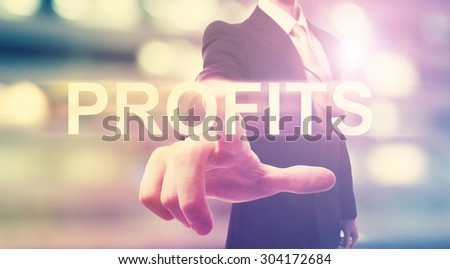 Businessman pointing at PROFITS on blurred city background - stock photo
