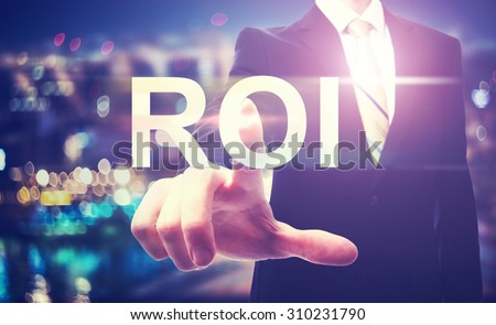 Businessman pointing at ROI (return on investment) on blurred city background - stock photo