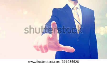 Businessman pointing at something on abstract light background - stock photo