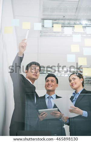 Businessman pointing at stickers with business ideas on glass wall