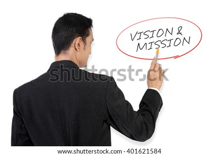 "Businessman pointing at ""Vision & Mission"" handwritten text on white board with his pen"
