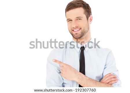 Businessman pointing copy space. Handsome young man in shirt and tie looking at camera and pointing away while standing isolated on white background - stock photo