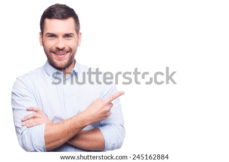 Businessman pointing copy space. Handsome young man in shirt looking at camera and pointing away while standing against white background - stock photo