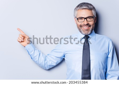 Businessman pointing copy space. Happy mature man in shirt and tie looking at camera and pointing away while standing against grey background - stock photo