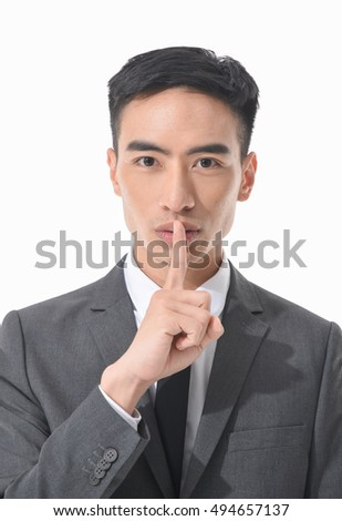 Businessman pointing finger over lips, asking for silence
