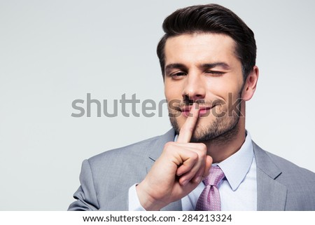 Businessman pointing finger over lips, asking for silence  over gray background. Looking at camera - stock photo