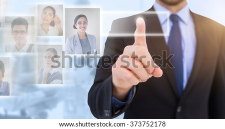Businessman pointing his finger at camera against blue background - stock photo