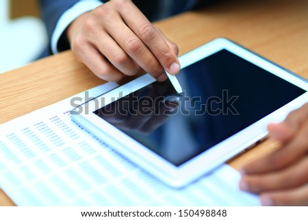 Businessman pointing on modern digital tablet  on screen at the workplace. - stock photo