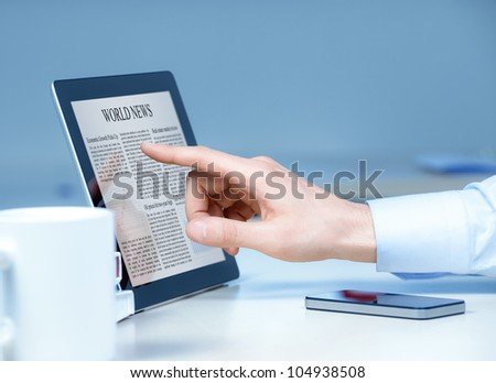 Businessman pointing on modern digital tablet with world news on screen at the workplace. - stock photo