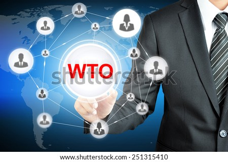 Businessman pointing on WTO (World Trade Organization) sign on virtual screen with people icons linked as network