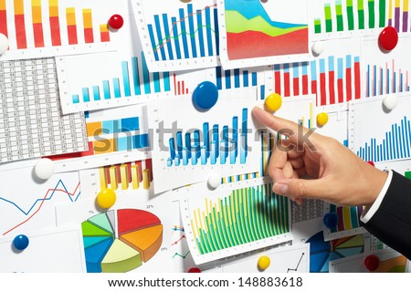 Businessman pointing out a graph. Choosing from a variety of documents.