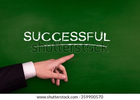 Businessman pointing SUCCESSFUL word on blackboard - stock photo