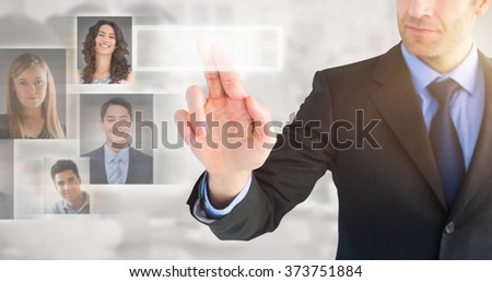 Businessman pointing these fingers at camera against grey background