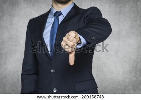 Businessman pointing thumbs down - stock photo