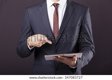 Businessman pointing to digital tablet against grunge background