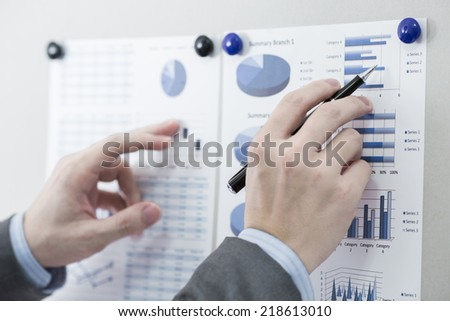 Businessman pointing to flip board with chart in office - stock photo