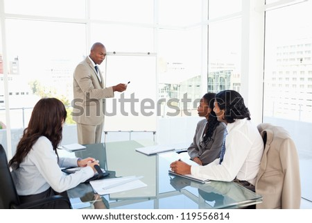 Businessman pointing to something on the flipchart to give explanations to his team