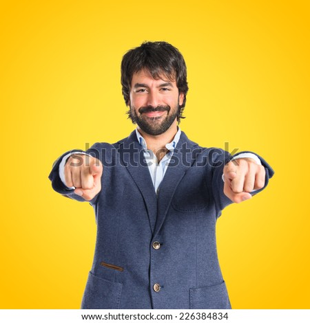 Businessman pointing to the front over yellow background - stock photo