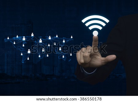 Businessman pointing to wi-fi button with light blue world map connection on city tower, Technology and internet concept, Elements of this image furnished by NASA - stock photo