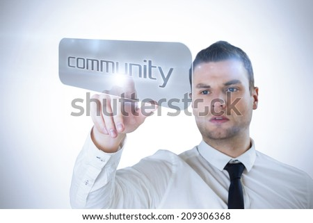 Businessman pointing to word community against white background with vignette