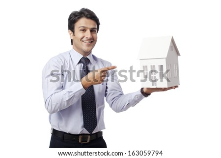 Businessman pointing towards a model home - stock photo