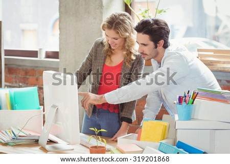 Businessman pointing towards computer in creative office - stock photo
