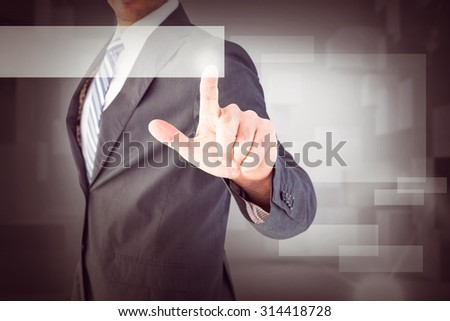 Businessman pointing with his finger against abstract white room - stock photo