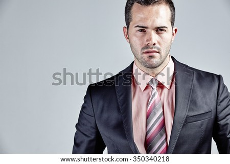 Businessman portrait isolated over grey - stock photo