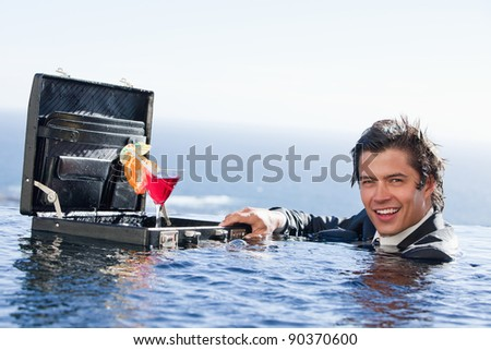 Businessman posing with a cocktail in a briefcase in a swimming pool