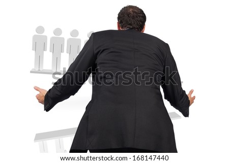 Businessman posing with arms out against white scales with human figures