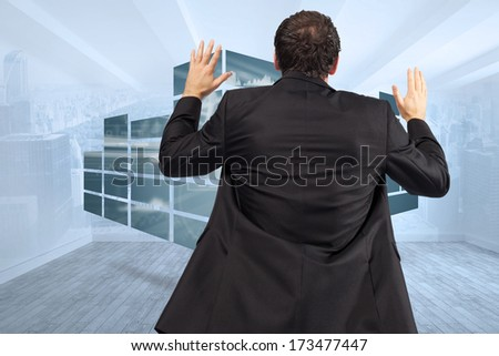 Businessman posing with arms raised against city scene in a room