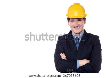 Businessman posing with folded arms wearing safety helmet