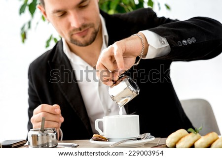 Businessman pouring milk to the cup of coffee at the restaurant